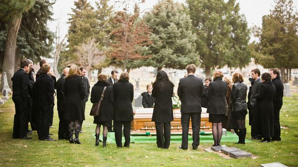 A group of people dressed in all black attending an outdoor funeral. They all have their back to the camera and they are looking at a casket on the ground. There are several trees in the background, and the group and standing on grass.