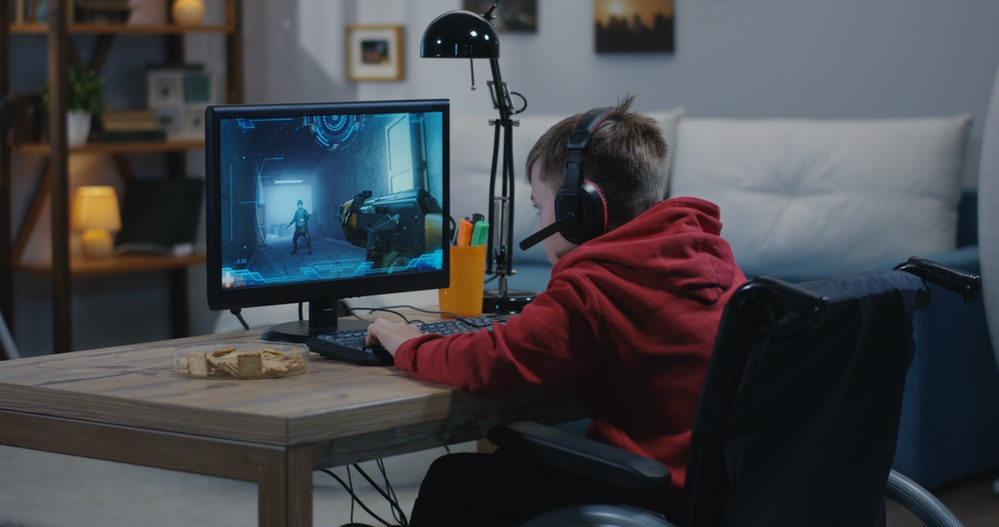 A medium wide shot of a disable young gamer playing video games online while sitting on his wheelcha...