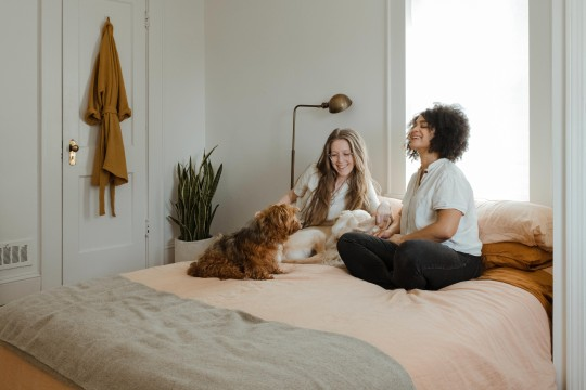 two girls with dog on bed