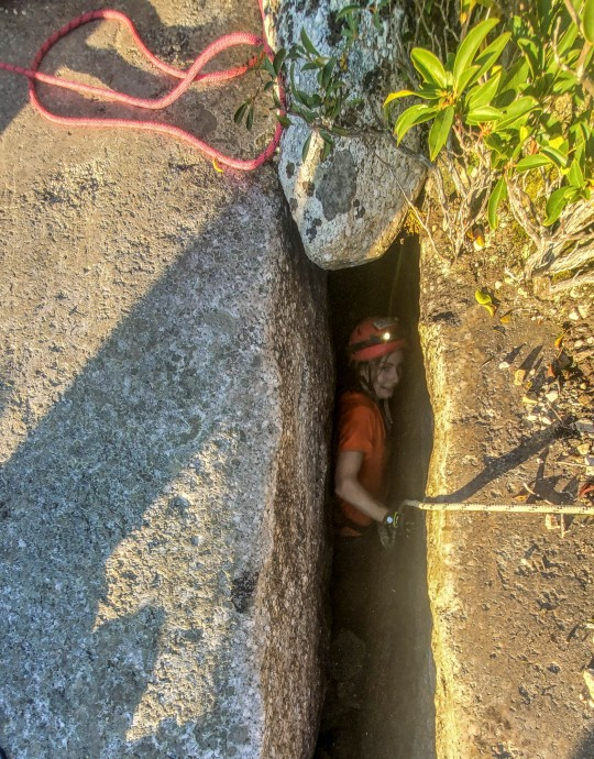 This photo provided by New York State Parks on Wednesday, Oct. 13, 2021, shows parks official Jessica Van Ord entering a fissure to rescue a 12-year-old dog named Liza, found trapped after five days deep inside the narrow, rocky crevice at Minnewaska State Park Preserve in Kerhonkson, N.Y. A dog trapped for five days deep inside a narrow, rocky crevice at a state park north of New York City was rescued unharmed ??? though it was hungry and thirsty, parks officials said Wednesday.(New York State Parks via AP)