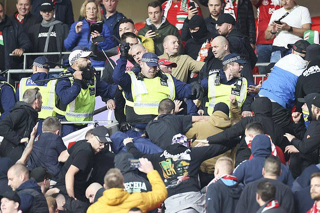 British police officers strike Hungary fans with batons during unrest at Wembley on Tuesday