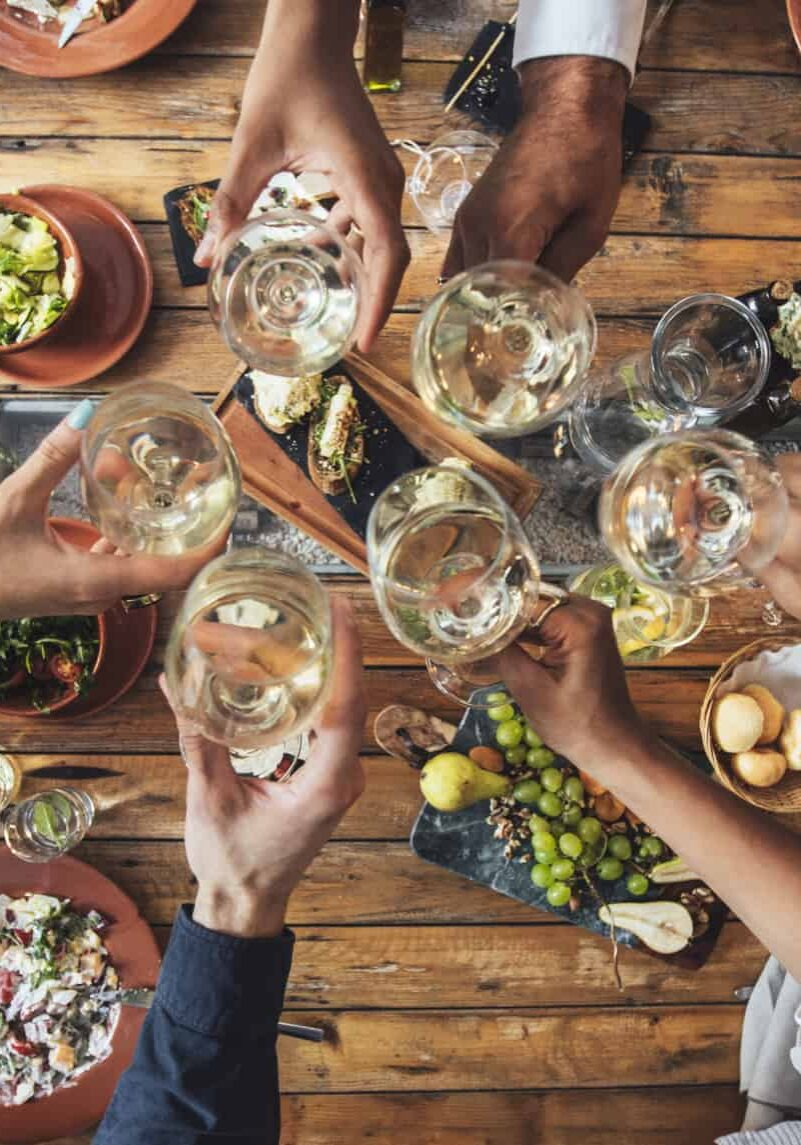 Hands of a group of people cheering with wine and rising glasses on celebration at restaurant.