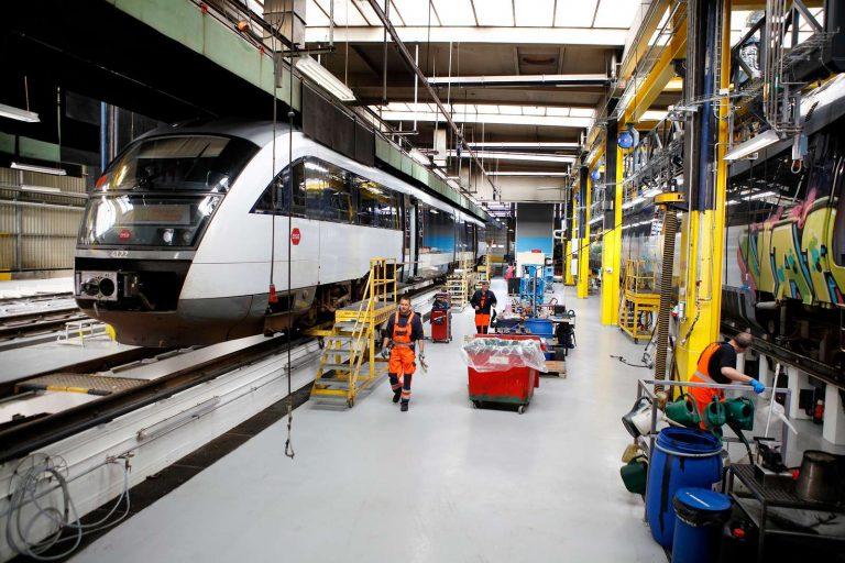 Et tog holder på værksted i Fredericia hvor mekanikere i arbejdstøj er igang med at reparere toget