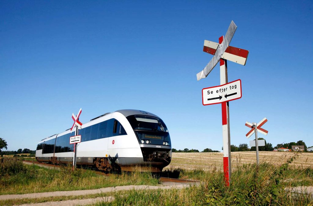 En Desiro tog kører over en jernbaneoverskæring en sommerdag hvor solen skinner fra en blå himmel