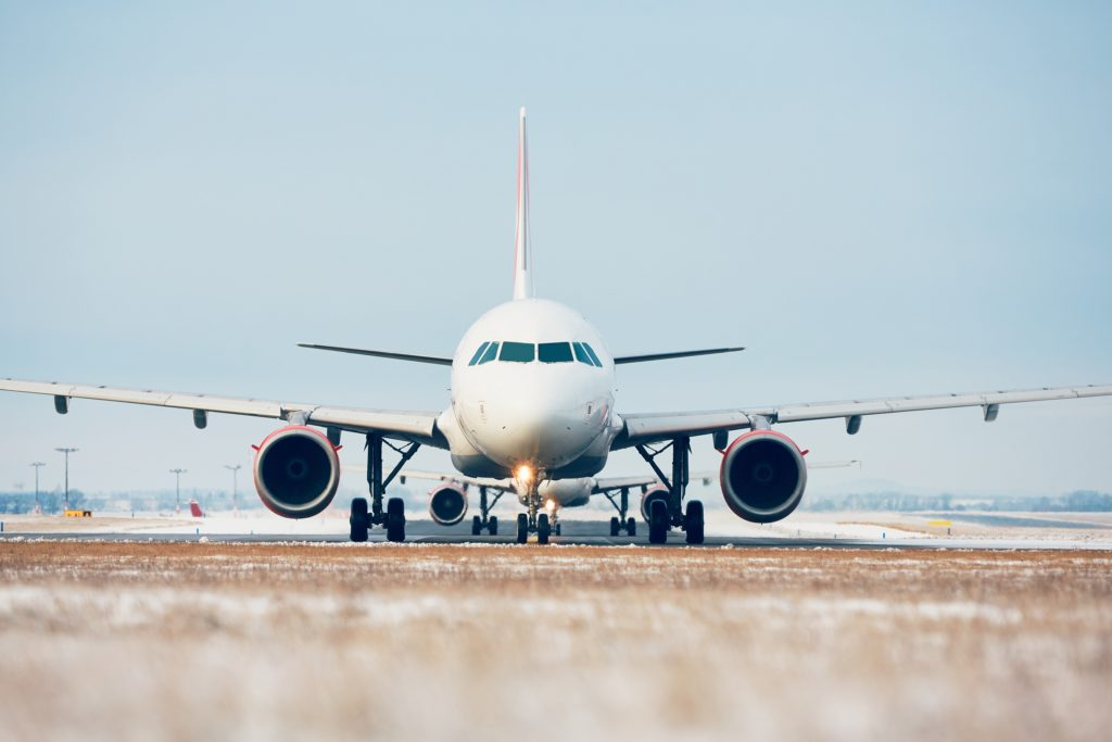 Airport in winter. Airplanes are taxiing to the runway for take off.