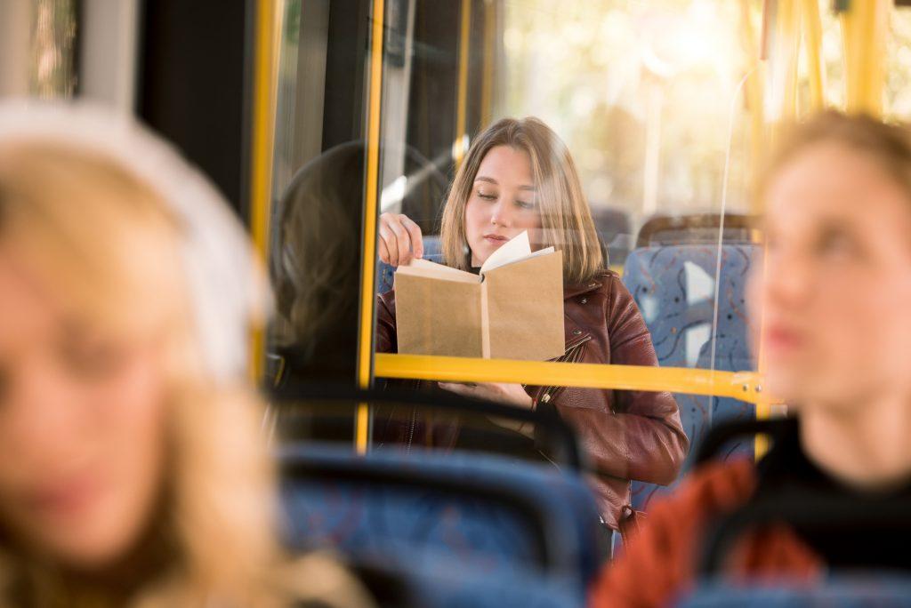 Kvinde læser en bog i bussen