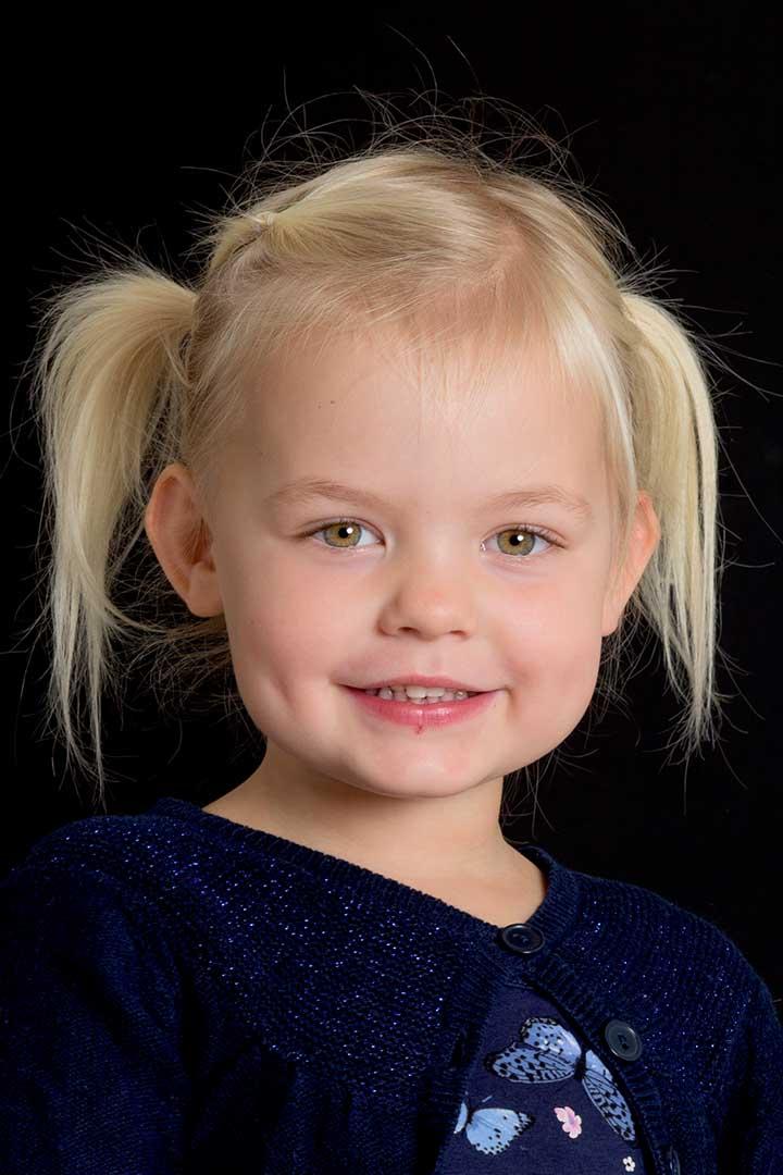 Klassisk børnehave-portræt af Mathilde på sort baggrund