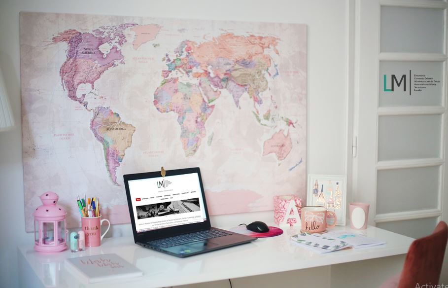 Laptop on desk in front of pink world map