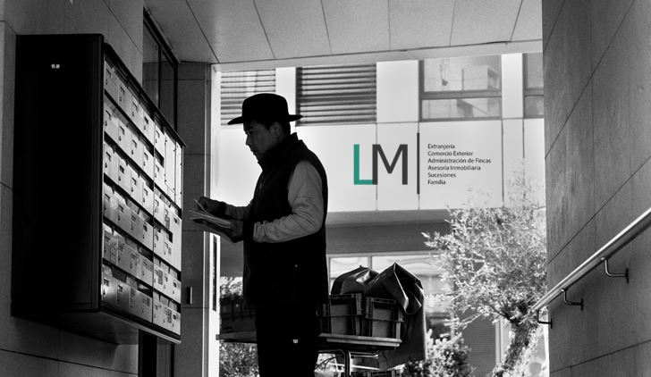 Postman puts mail in mail boxes & LM Abogados logo