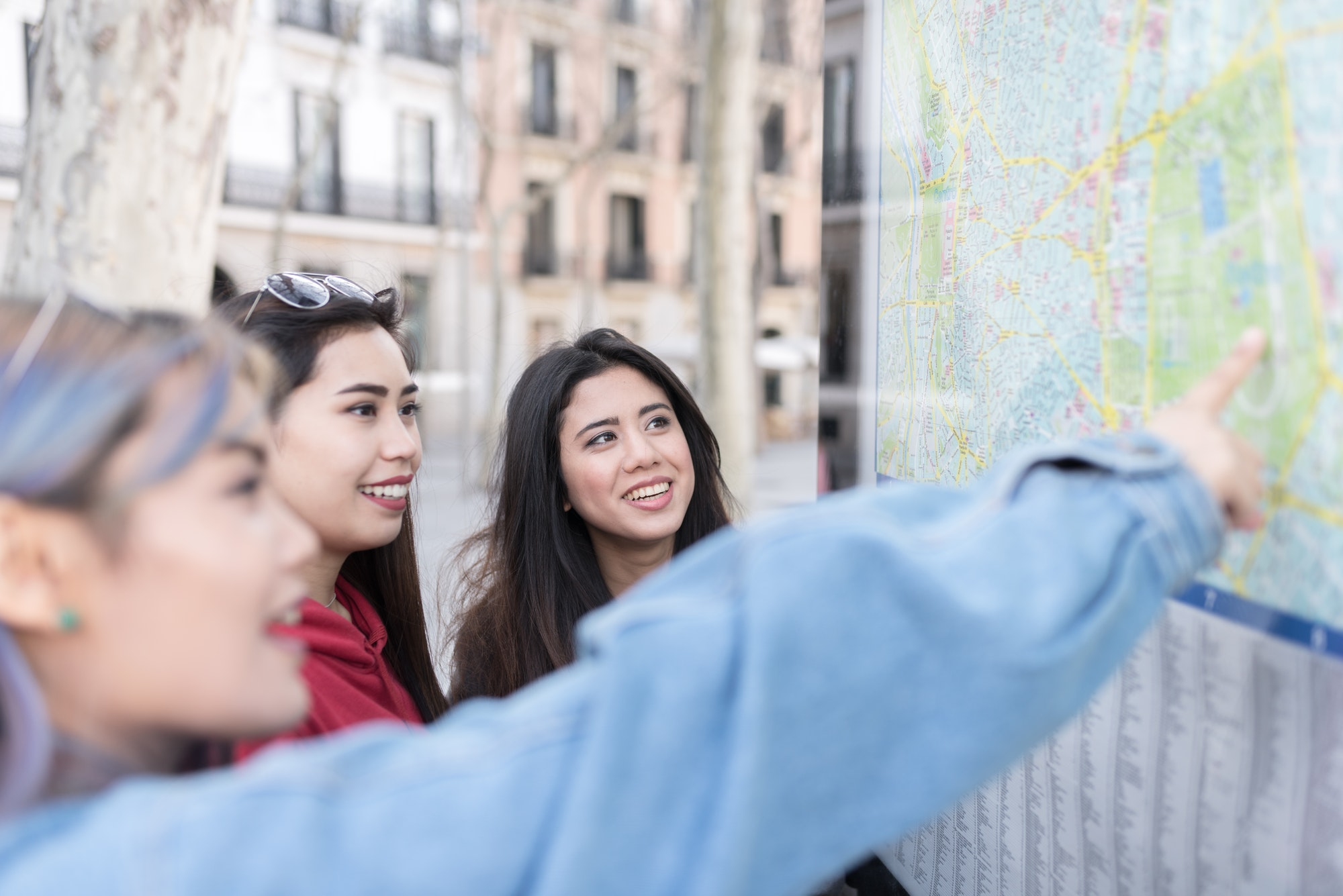 philippine friends women in Madrid looking a map on the street