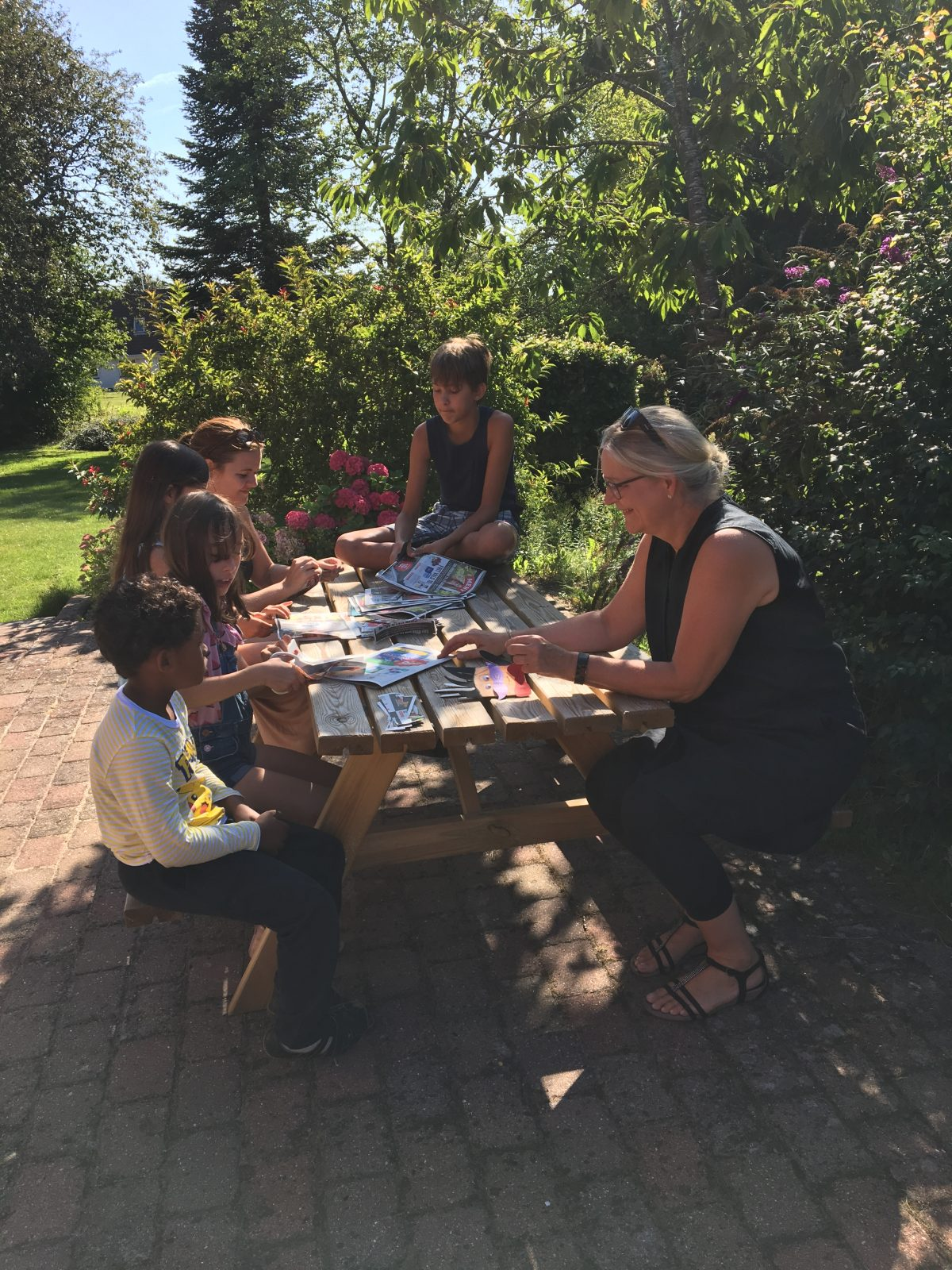 kids and adult sitting at the table outside