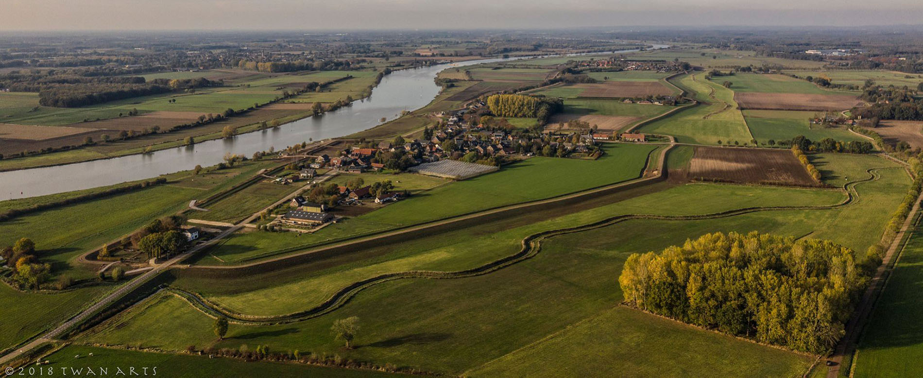 """Het dorpje Aijen is gelegen op een rivierduin langs de Maas. Het kent een eeuwenoude geschiedenis, waarschijnlijk van meer dan 1500 jaar. Het dorp en haar bijbehorende """"buurtschappen"""" vormen een hechte gemeenschap van nu 350 inwoners. In vroegere tijden werd de broodwinning in dit landelijke dorp voornamelijk verkregen uit boerenbedrijfjes, klompenmakers, mandenmakers, een bakkerij, een hoefsmid en veel cafeetjes. Sindsdien is er veel veranderd."""