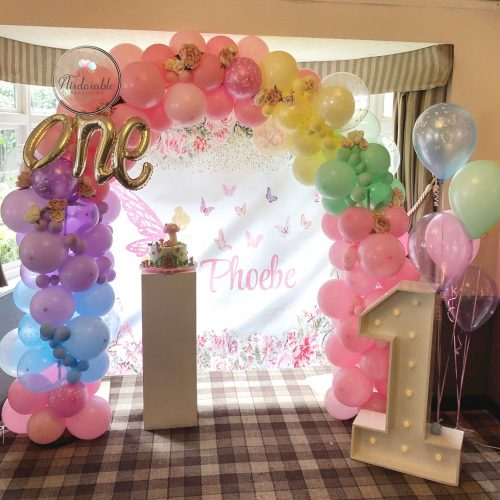 rainbow balloon arch with pink blue purple green balloons and number 1 and plinth