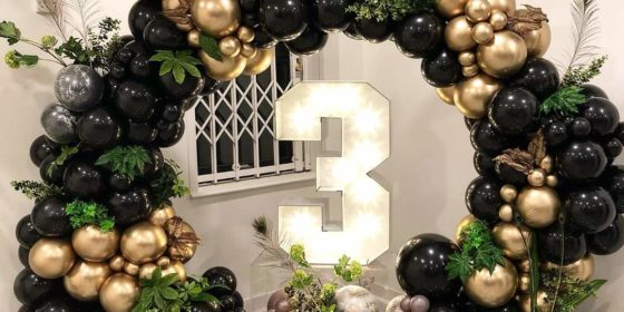 black gold and green balloon garland on a balloon hoop with foliage for Balloon Decor Services