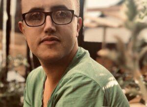 Porträttbild på Adrian Mikkelsen. Han har ljusgrön tröja, glasögon med mörka bågar och tittar in i kameran