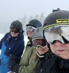 en bild på familjen Åberg (Lotta, Torbjörn, Oliver och Hugo), tagen i en skidbacke. Alla har täckkläder, hjälmar och skidglasögon, i Torbjörns glasögon reflekteras hans hand som tar fotot. Det är lite disigt väder och i bakgrunden skymtar granar.
