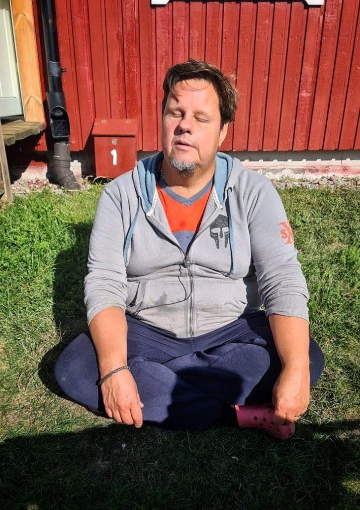 Ansvarig ledare Anderz sitter i skräddarställning i solen, bakom en röd husvägg.