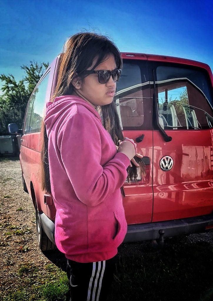 Angelina framför minibussen, hon har rosa tröja, långt brunt hår och solglasögon