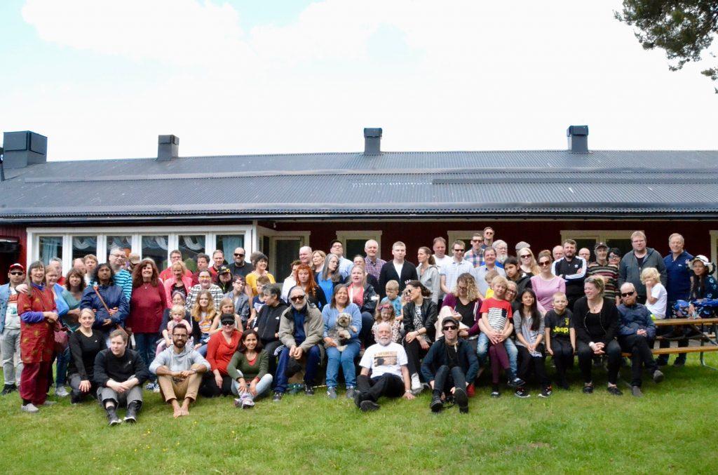 Gruppfoto från Aktiva Synskadades 50-årsjubileum, sommaren 2019. Bilden är tagen framför ett av husen på Mälargårdarna.