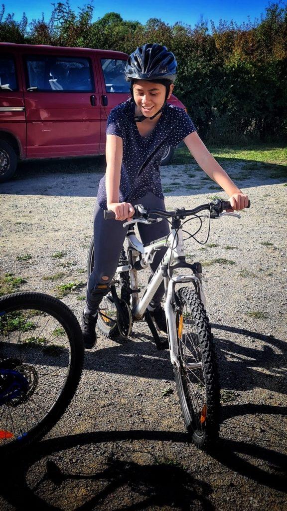 Flicka på cykel, redo att ge sig iväg.
