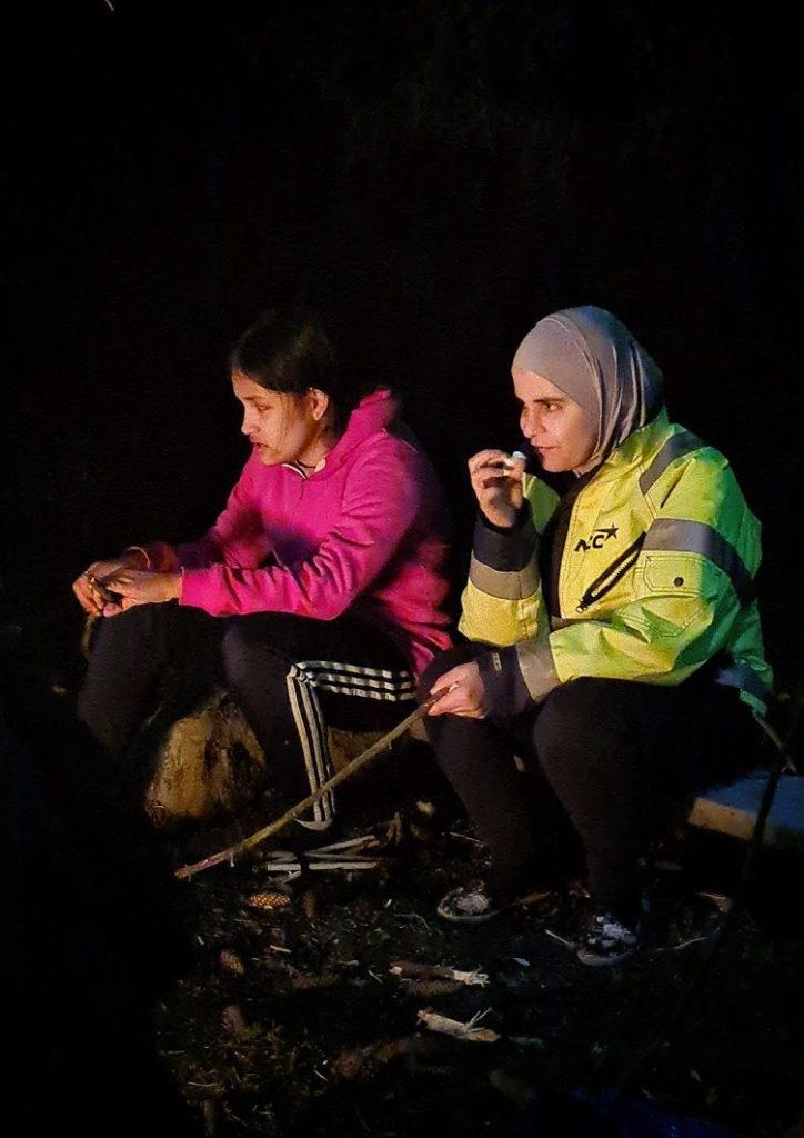 Barn och vuxna sitter vid elden