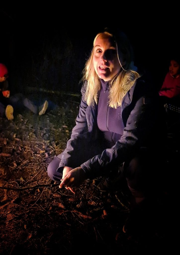 Kvinna sitter vid lägerelden. Hon tittar in i kameran. Hennes ansikte är upplyst av elden