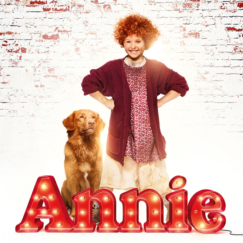 En bild på Annie med rött, lockigt hår som tittar busigt rakt in i kameran, bredvid sig en brun hund. Längst ned texten Annie i rött och med lampor på.