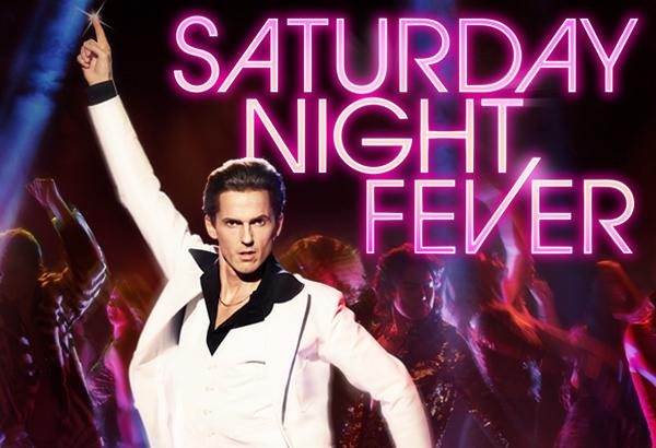 David Lindgren står i den klassiska dansposen från filmen, med ena armen pekandes rakt upp. Han har vit kostym och svart skjorta. Texten Saturday Night Fever i rosa neon till höger i bild.