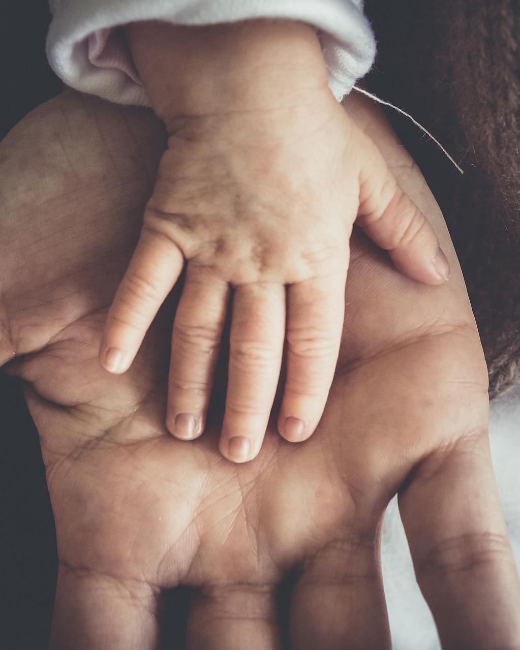 voksenhand og barnehand holder hverandre med kjaerlighet etter akutthjelp fra alle barna sover