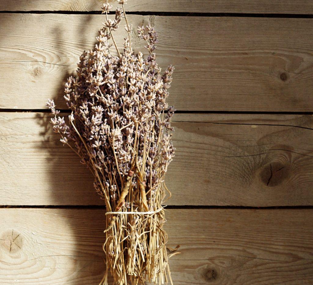 Getrockneter Lavendelstrauß liegt auf einem Holztisch.