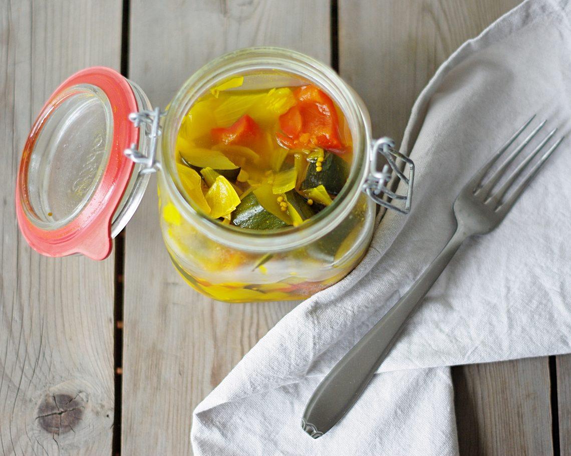 geöffnetes Bügelglas mit eingelegten Zucchini und Paprika, daneben Stoffserviette und alte Gabel da drauf