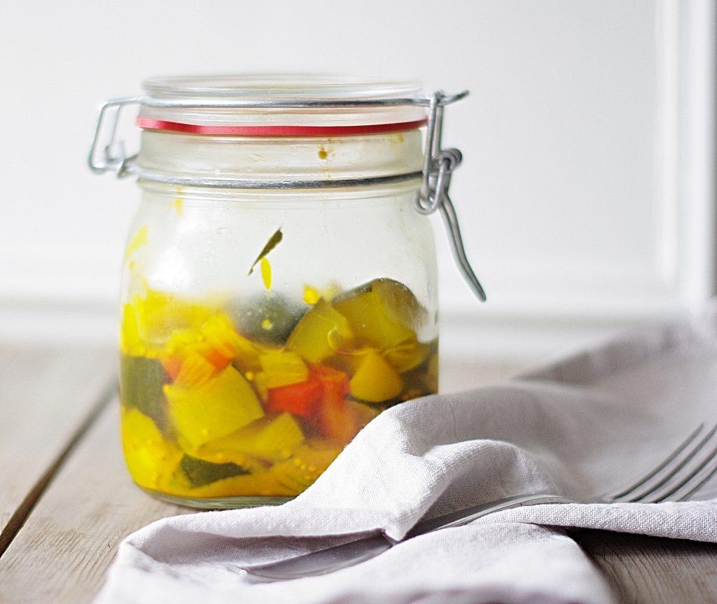 verschlossenes Bügelglas mit eingelegten Zucchini und Paprika, Stoffserviette und Gabel