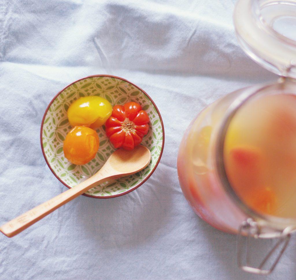 Schälchen mit fermentierten Tomaten mit Holzlöffel, daneben offenes Bügelglas