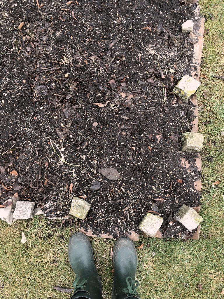 Pappe auf Rasen, Kompost auf der Pappe und Steine, Gummistiefel davor