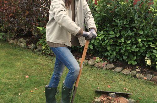 Gärtnerin bereitet Boden für Rasenkantenbleche vor
