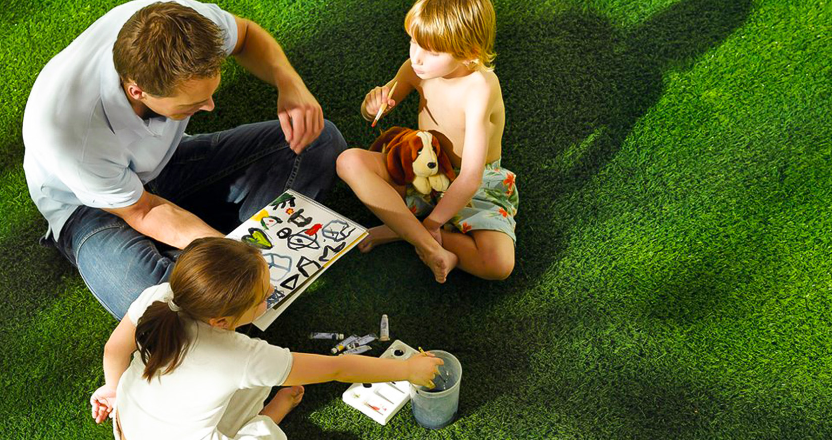 family sitting on artificial grass