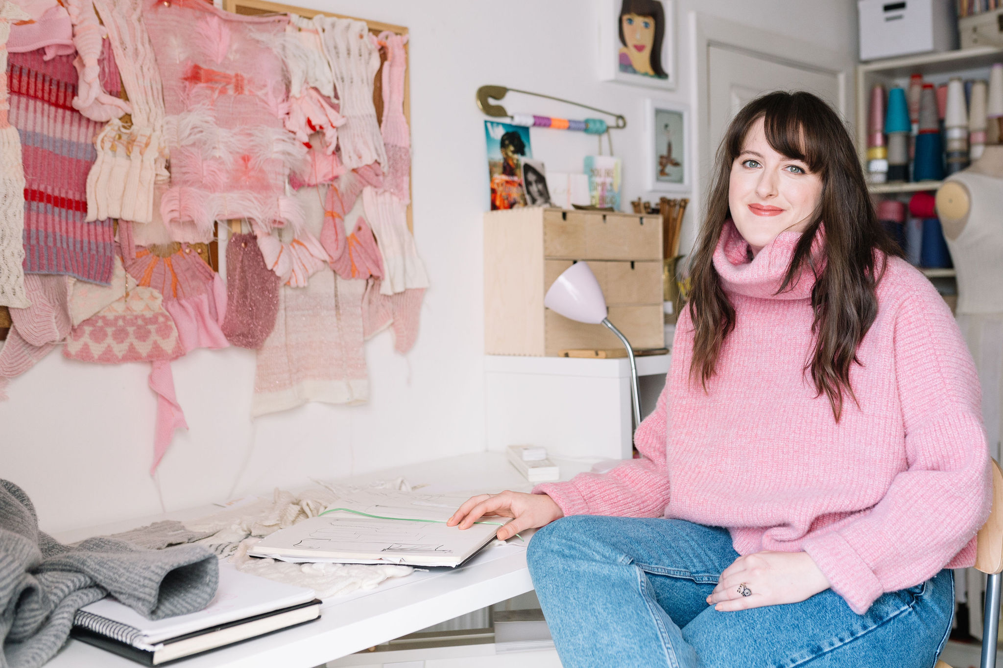Amber Hards sitting in her studio surrounded by knitting machine fabric swatches and sketchbooks