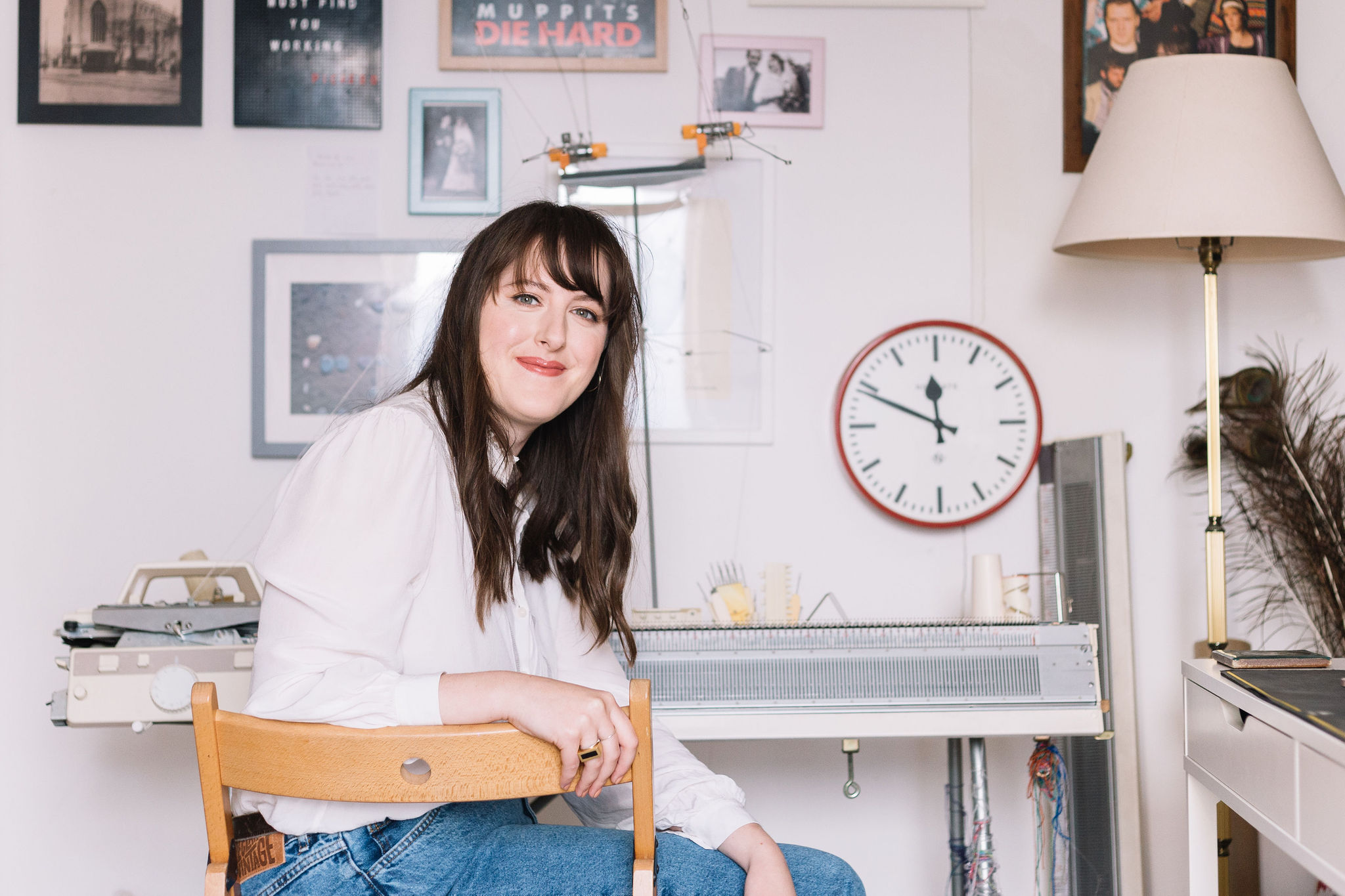Amber Hards sitting in a chair in front of her knitting machine