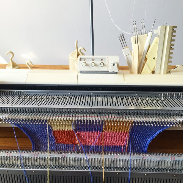 knitting machine with an intarsia swatch in bright colours being knit