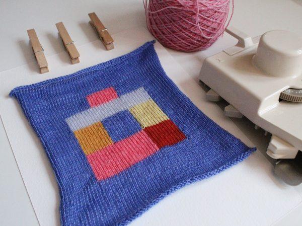intarsia fabric sample, pegs and intarsia carriage with ball of yarn
