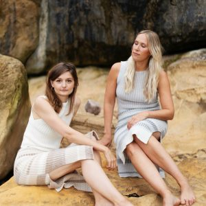 two models wearing amber hards knit tops and skirts sat on a beach