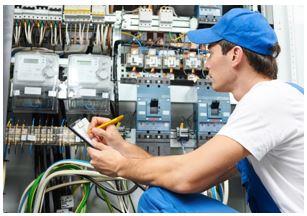 Electricistas montando un cuadro eléctrico complejo con varios diferenciales y muchos automáticos.