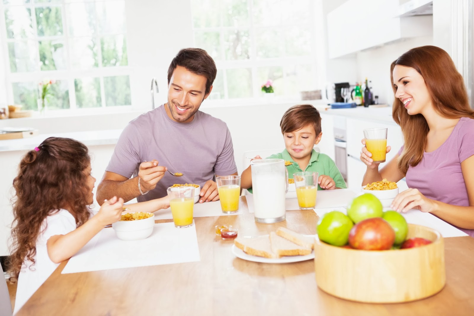 Reformas de cocinas. Pareja con niño y niña desayunando felices en la cocina.