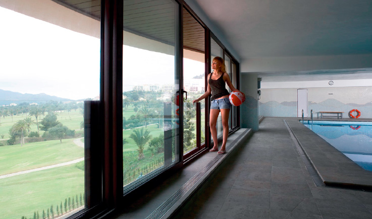 Mujer mirando a través de los cristales de unas puertas correderas de PVC, Sumum (Arcolinea, s.l.)