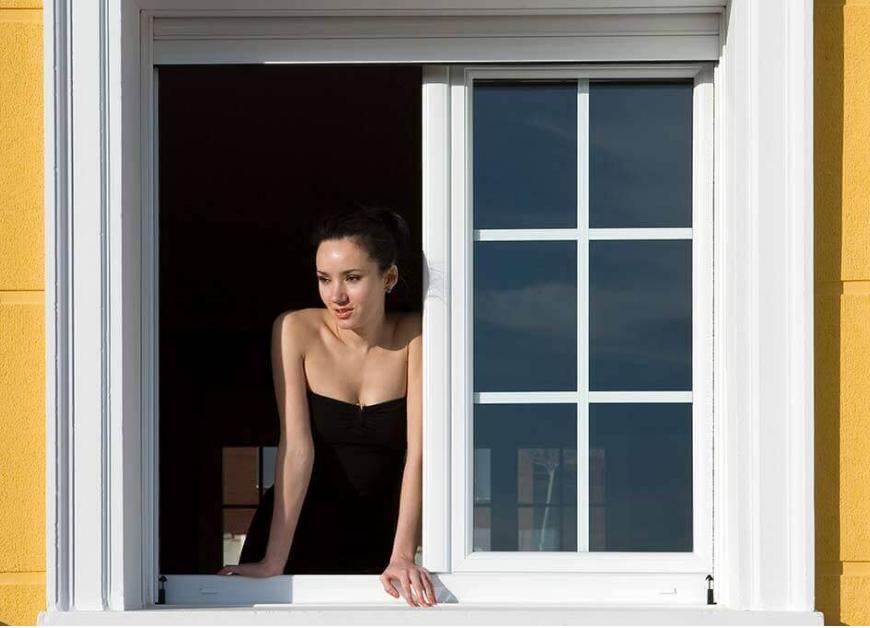 Mujer asomada en una ventana abatible Zendow de PVC blanco.