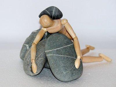 stick figure under rocks