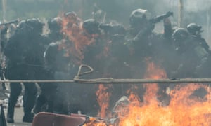 A riot police officer aims a teargas launcher at protesters at the Hong Kong Polytechnic University on 18 November.