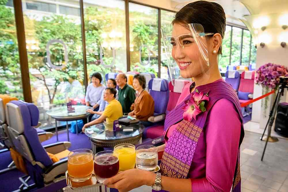 A Thai Airways flight attendant wearing a face shield as she serves drinks at a pop-up airplane-themed restaurant at the airline's headquarters in Bangkok September 10, 2020. — AFP pic