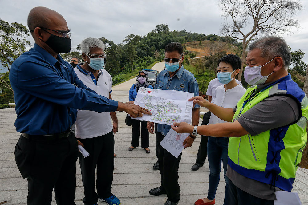 Penang Island Municipal Council Engineering Department Director PA Rajendran (centre) showing where the illegally conducted earthworks in Bukit Relau are being carried out on a map, September 14, 2020. — Picture by Sayuti Zainudin