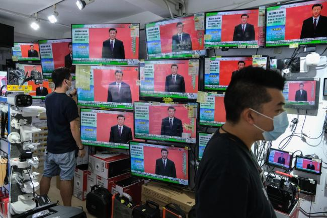 © Bloomberg. President Xi Jinping's speech in Shenzhen is broadcasted inside a store in Hong Kong, Oct. 14.